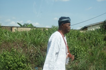 A older gentleman wearing traditional hat (Yoruba style) with traditional beads